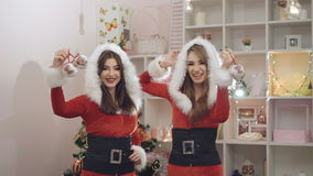 Two funny ladies dancing, smiling with Christmas toys in 4K.  stock video