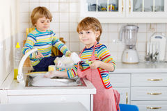 Two funny little boy friends washing dishes in domestic kitchen Royalty Free Stock Images