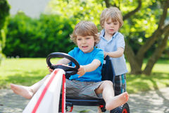 Two funny little boys having fun with race car outdoors Royalty Free Stock Photos