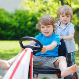 Two funny little boys having fun with race car outdoors Royalty Free Stock Image