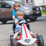 Two funny little boys having fun with race car outdoors Stock Photo