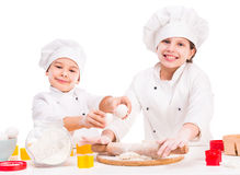 Two funny little cooks preparing dough Stock Photo