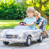 Two funny little friends playing with big old toy car Stock Images