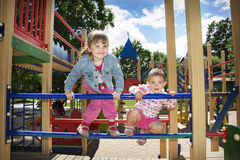 Two funny little girl playing on the playground. Royalty Free Stock Photos