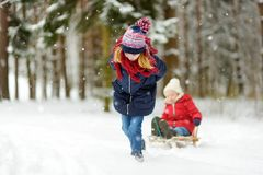 Two funny little girls having fun with a sleigh in beautiful winter park. Cute children playing in a snow. royalty free stock photography