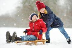 Two funny little girls having fun with a sleigh in beautiful winter park. Cute children playing in a snow. stock image