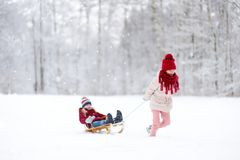 Two funny little girls having fun with a sleight in beautiful winter park. Cute children playing in a snow. Stock Photos
