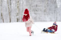 Two funny little girls having fun with a sleight in beautiful winter park. Cute children playing in a snow. Royalty Free Stock Photography