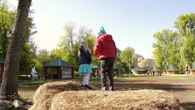 Two funny little girls jumping from one haystack to another. Slow motion stock video