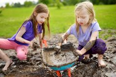 Two funny little girls playing in a large wet mud puddle on sunny summer day. Children getting dirty while digging in muddy soil. Messy games outdoors stock photography