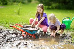 Two funny little girls playing in a large wet mud puddle on sunny summer day. Children getting dirty while digging in muddy soil. Messy games outdoors royalty free stock photos