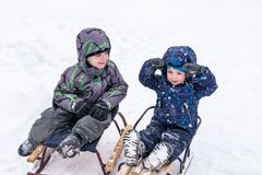 Happy friends having fun with snow. Two funny little kid boys in colorful clothes playing outdoors. Active leisure with children in winter on cold snowy days Stock Photo