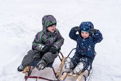 Happy friends having fun with snow. Two funny little kid boys in colorful clothes playing outdoors. Active leisure with children in winter on cold snowy days Royalty Free Stock Photography