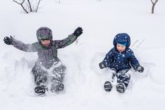 Happy friends having fun with snow. Two funny little kid boys in colorful clothes playing outdoors. Active leisure with children in winter on cold snowy days Royalty Free Stock Image
