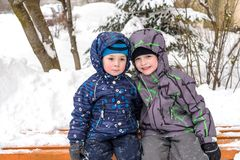 Happy friends having fun with snow. Two funny little kid boys in colorful clothes playing outdoors. Active leisure with children in winter on cold snowy days Royalty Free Stock Photos