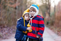 Two funny little kid sibling boys hugging on cold day Stock Photos