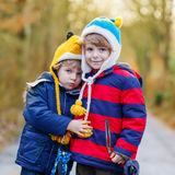 Two funny little kid sibling boys hugging on cold day Stock Images
