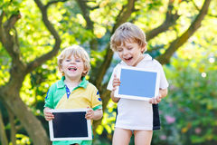 Two funny little kids happy abount tablets pc Royalty Free Stock Photo