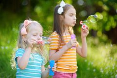 Two funny little sisters blowing soap bubbles outdoors Stock Photo