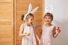 Two funny little sisters in the dresses with white rabbit`s ears on their heads have fun with dyed eggs in their hands stock photo