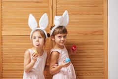 Two funny little sisters in the dresses with white rabbit`s ears on their heads have fun with dyed eggs in their hands royalty free stock image