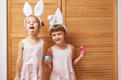 Two funny little sisters in the dresses with white rabbit`s ears on their heads have fun with dyed eggs in their hands stock photography