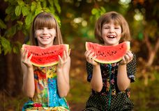 Two funny little sisters eating watermelon outdoors on warm and sunny summer day. Healthy food for kids. Two funny little sisters eating watermelon outdoors on stock image