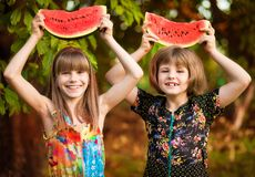 Two funny little sisters eating watermelon outdoors on warm and sunny summer day. Healthy food for kids. Two funny little sisters eating watermelon outdoors on royalty free stock photography