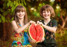 Two funny little sisters eating watermelon outdoors on warm and sunny summer day. Healthy food for kids. Two funny little sisters eating watermelon outdoors on stock photography