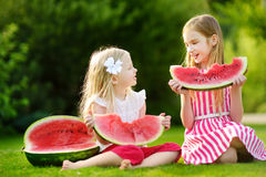 Two funny little sisters eating watermelon outdoors on warm and sunny summer day royalty free stock photos