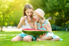 Two funny little sisters eating watermelon with the spoons outdoors on warm and sunny summer day. Healthy organic food for kids. stock photos