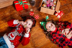 Two funny little sisters lie on the floor at home. Near Christmas tree royalty free stock image