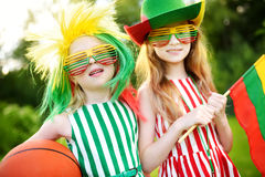 Two funny little sisters supporting and cheering their national basketball team during basketball championship Royalty Free Stock Photography