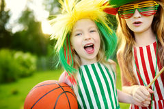 Two funny little sisters supporting and cheering their national basketball team during basketball championship Royalty Free Stock Photos