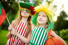 Two funny little sisters supporting and cheering their national basketball team during basketball championship Royalty Free Stock Image