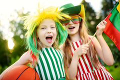 Two funny little sisters supporting and cheering their national basketball team during basketball championship Stock Photography