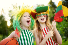 Two funny little sisters supporting and cheering their national basketball team during basketball championship Royalty Free Stock Photo