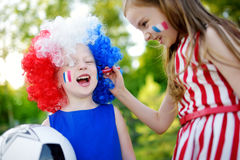 Two funny little sisters supporting and cheering their national football team Stock Images