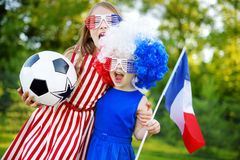 Two funny little sisters supporting and cheering their national football team Royalty Free Stock Images