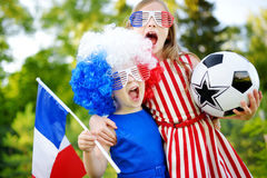 Two funny little sisters supporting and cheering their national football team Royalty Free Stock Image