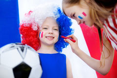 Two funny little sisters supporting and cheering their national football team Royalty Free Stock Photography