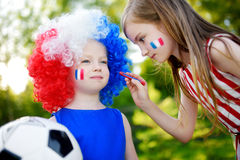 Two funny little sisters supporting and cheering their national football team Stock Photography