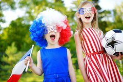 Two funny little sisters supporting and cheering their national football team Stock Photos