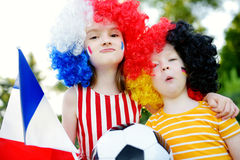 Two funny little sisters supporting and cheering their national football teams Stock Photography