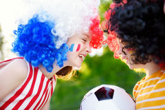 Two funny little sisters supporting and cheering their national football teams Royalty Free Stock Image