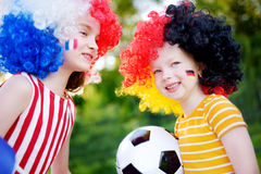 Two funny little sisters supporting and cheering their national football teams Stock Photos
