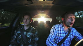 Two funny men driving fast in a car in sunny day. In full HD stock video