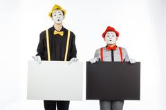 Two funny mimes holding a white blank on a white background. royalty free stock photo
