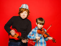 Two funny red-hair brothers playing music Stock Photography