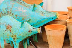 Two funny rusty metal blue pigs on wooden table. Interior or garden decoration.  royalty free stock photo